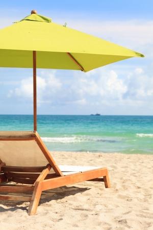 Umbrella and lounge chair along the shoreline of Miami Beach