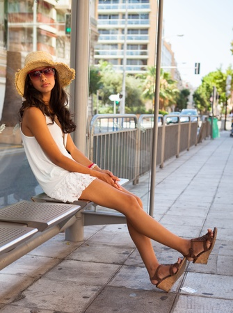 Beautiful young woman waiting for a bus in Nice, France