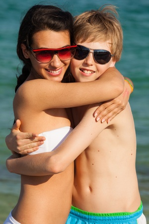 multiracial children: Teenagers in a loving embrace enjoying the beach