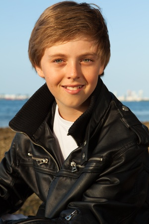 Handsome young teenager wearing a black leather jacket enjoying the beach in Miami  Stock Photo