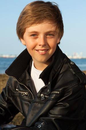 Knappe jonge tiener met een zwarte leren jas genieten van het strand in Miami Stockfoto
