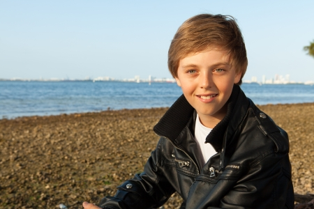 europeans: Handsome young teenager wearing a black leather jacket enjoying the beach in Miami  Stock Photo