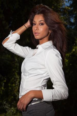 asian american: Beautiful young mixed race woman in a fashion pose outdoors  Stock Photo