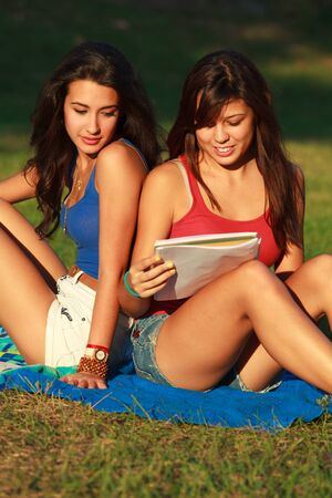 Beautiful multicultural young college women studying outdoors on campus Stock Photo - 16963708