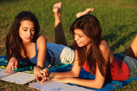 Beautiful multicultural young college women studying outdoors on campus  Stock Photo - 16963732
