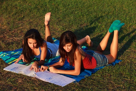 Beautiful multicultural young college women studying outdoors on campus  photo