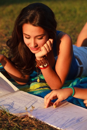Beautiful multicultural young college woman studying outdoors on campus  photo