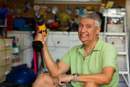 ガレージの電動工具を保持しているハンサムな中年男
