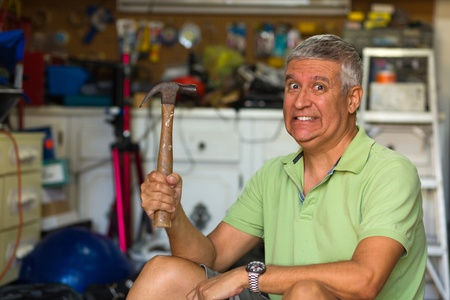 male age 40's: Handsome middle age man holding a hammer in a garage  Stock Photo