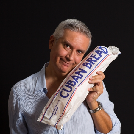 Handsome middle age man  holding a loaf of Cuban bread on a black background