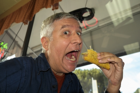 taco: Close up view of a man eating a taco in a restaurant