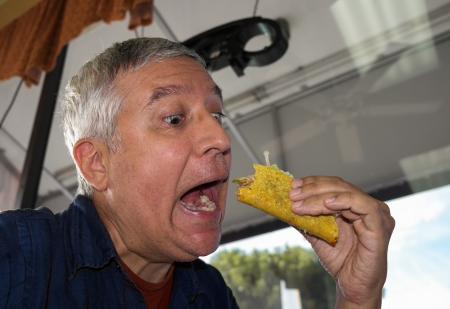 taco tortilla: Close up view of a man eating a taco in a restaurant