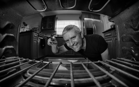 black appliances: Fish eye view of a handsome middle age man looking inside an oven in a home kitchen in black and white