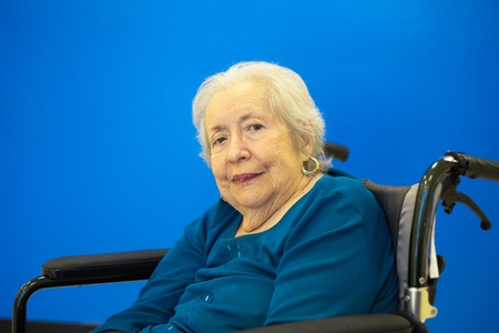 Elderly 80 plus year old woman portrait with a blue background  photo