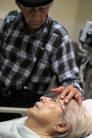 Elderly 80 plus year old woman in a hospital bed with her caring husband  photo