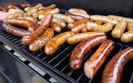 grill: Fresh sausage and hot dogs grilling outdoors on a gas barbeque grill  Stock Photo