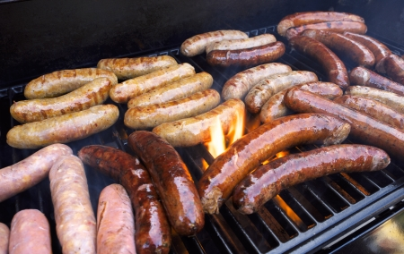 feast: Fresh sausage and hot dogs grilling outdoors on a gas barbeque grill  Stock Photo