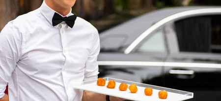 Waiter serving appetizers at a luxurious gathering  Imagens