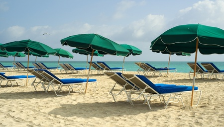 Colorful lounge chairs and umbrellas along the shoreline in beautiful Miami Beach  photo