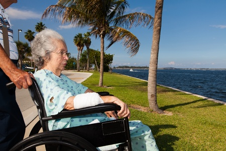 Elderly 80 plus year old woman in a wheel chair convalescing outdoors in a bay setting
