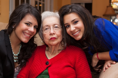 latino family: Grandmother with granddaughters in a home setting  Stock Photo