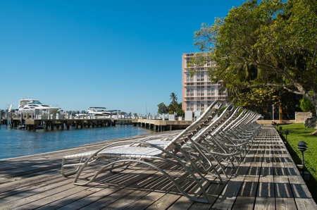wooden dock: Row of white lawn chairs outdoors in a condo setting