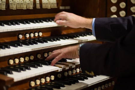 piano: Cierre de vista de un organista tocando un �rgano de tubos con el desenfoque de movimiento Foto de archivo