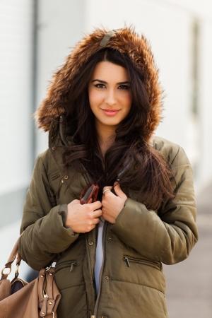 winter fashion: Beautiful young multicultural woman outdoors wearing a winter fur coat