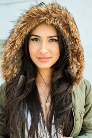 Beautiful young multicultural woman outdoors wearing a winter fur coat  photo