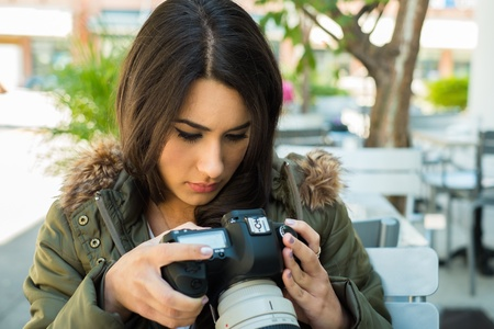 Beautiful young woman outdoors looking at pictures on a camera display. photo