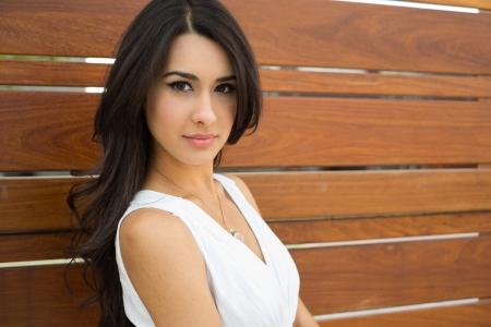 American Indian: Hermosa mujer joven multicultural al aire libre con un fondo de madera