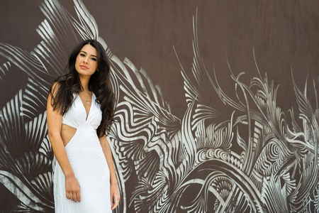 Beautiful young multicultural woman outdoors with a graffiti background. photo