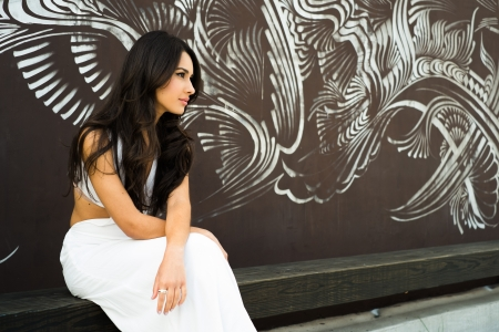 graffiti background: Beautiful young multicultural woman outdoors with a graffiti background.