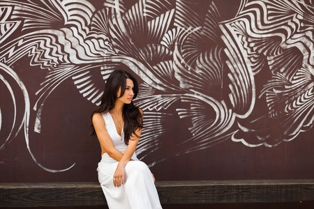 Beautiful young multicultural woman outdoors with a graffiti background  photo