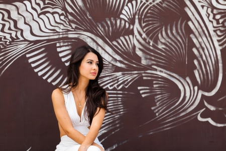 graffiti background: Beautiful young multicultural woman outdoors with a graffiti background  Stock Photo