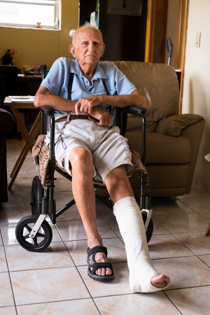 pierna rota: anciano se sienta en la silla de ruedas en una casa