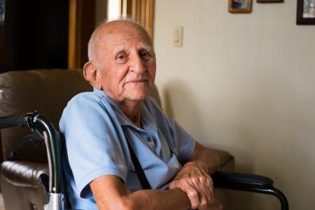 ancianos felices: anciano se sienta en la silla de ruedas en un hogar