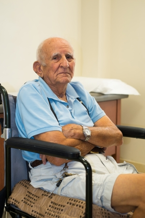 old man sitting: old man in a doctor office setting  Stock Photo