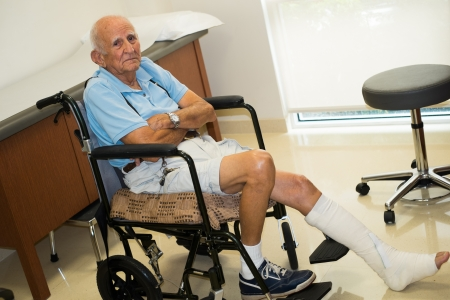 broken leg: old man in a doctor office setting  Stock Photo