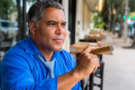 hombre fumando puro: Hombre de la edad media hispana hermoso que fuma un cigarro al aire libre en un restaurante