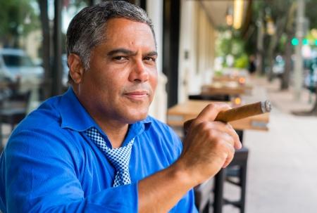 hombre fumando puro: Hombre de la edad media hispana hermoso que fuma un cigarro al aire libre en un restaurante.