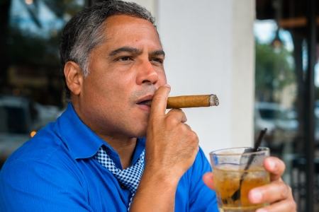 Handsome middle age Hispanic man smoking a cigar with a cocktail. photo