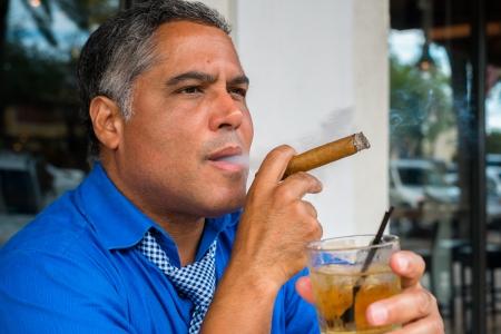 hombre fumando puro: Apuesto hombre hispanos de mediana edad que fuma un cigarro con un cóctel. Foto de archivo