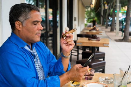Handsome middle age Hispanic man smoking a cigar while texting outdoors in a restaurant. photo