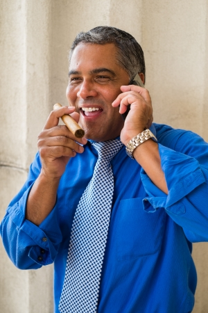 Handsome middle age Hispanic man smoking a cigar outdoors and speaking in a wireless phone in a urban setting. photo
