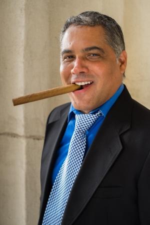 hombre fumando puro: Hombre de la edad media hispana hermoso que fuma un cigarro al aire libre en un entorno urbano. Foto de archivo
