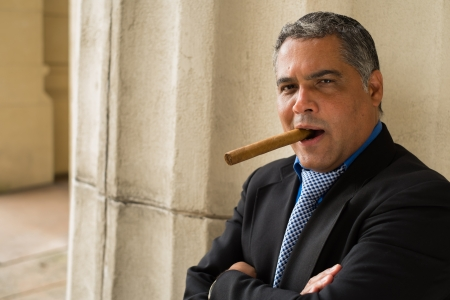 Handsome middle age Hispanic man smoking a cigar outdoors in a urban setting. photo