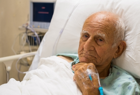 Elderly 80 plus year old man recovering from surgery in a hospital bed  photo