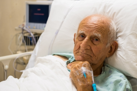 recovering: Elderly 80 plus year old man recovering from surgery in a hospital bed