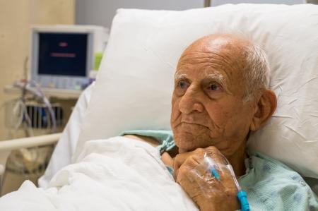 Ouderen 80 plus jaar oude man herstellen van een operatie in een ziekenhuis bed